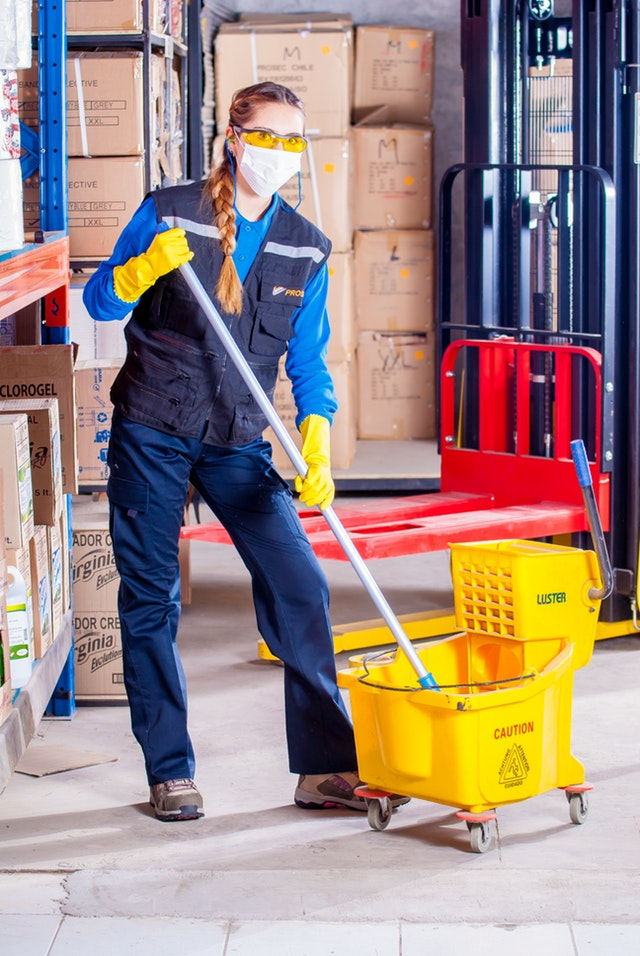Woman With a Mop and Bucket in a Warehouse