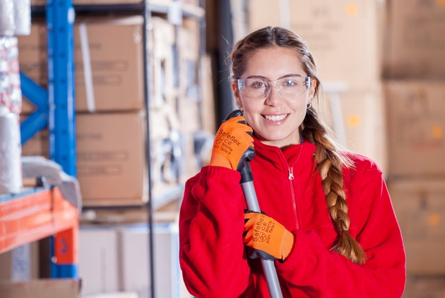 Michigan Employment Services Woman Working in Warehouse Holding Broom